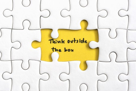 Jigsaw puzzle piece with two missing and hand writing letters word think outside the box, Quotes business concept